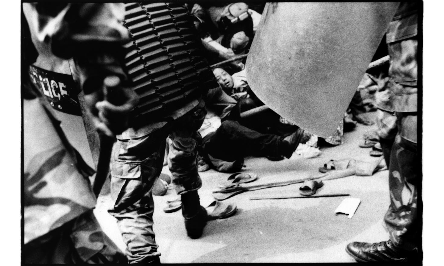 A woman is burried under other protestors bodies, while riot police keep beating them up with bamboo sticks, Katmandu Nepal 22d of April 2006