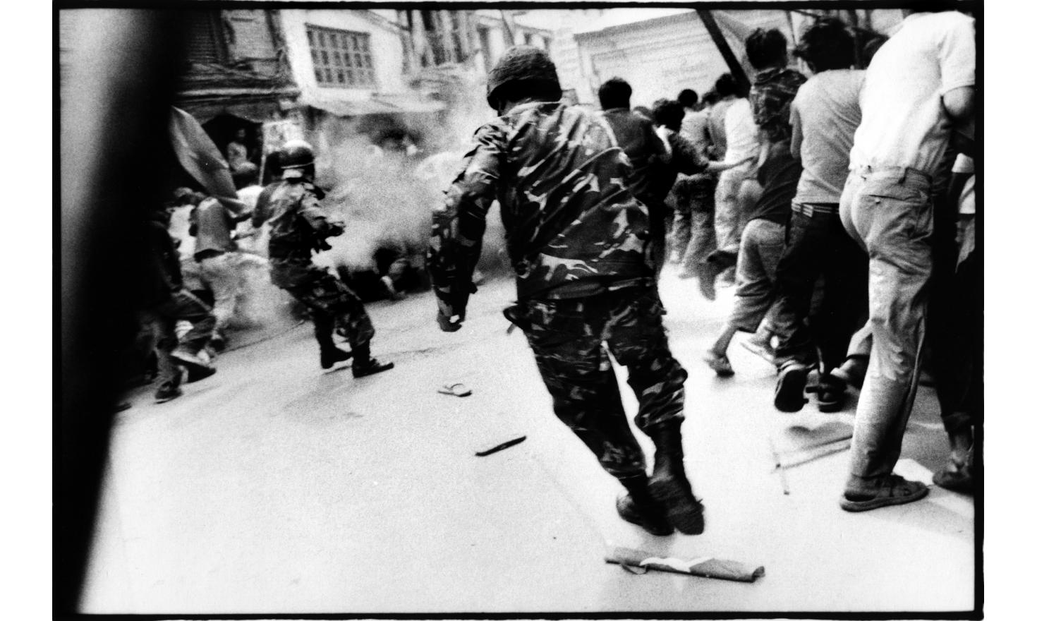 Riot police is charging and firing tear gas over protestors in the narrow streets of the center Kathmandu: Asan chow 22d of April 2006