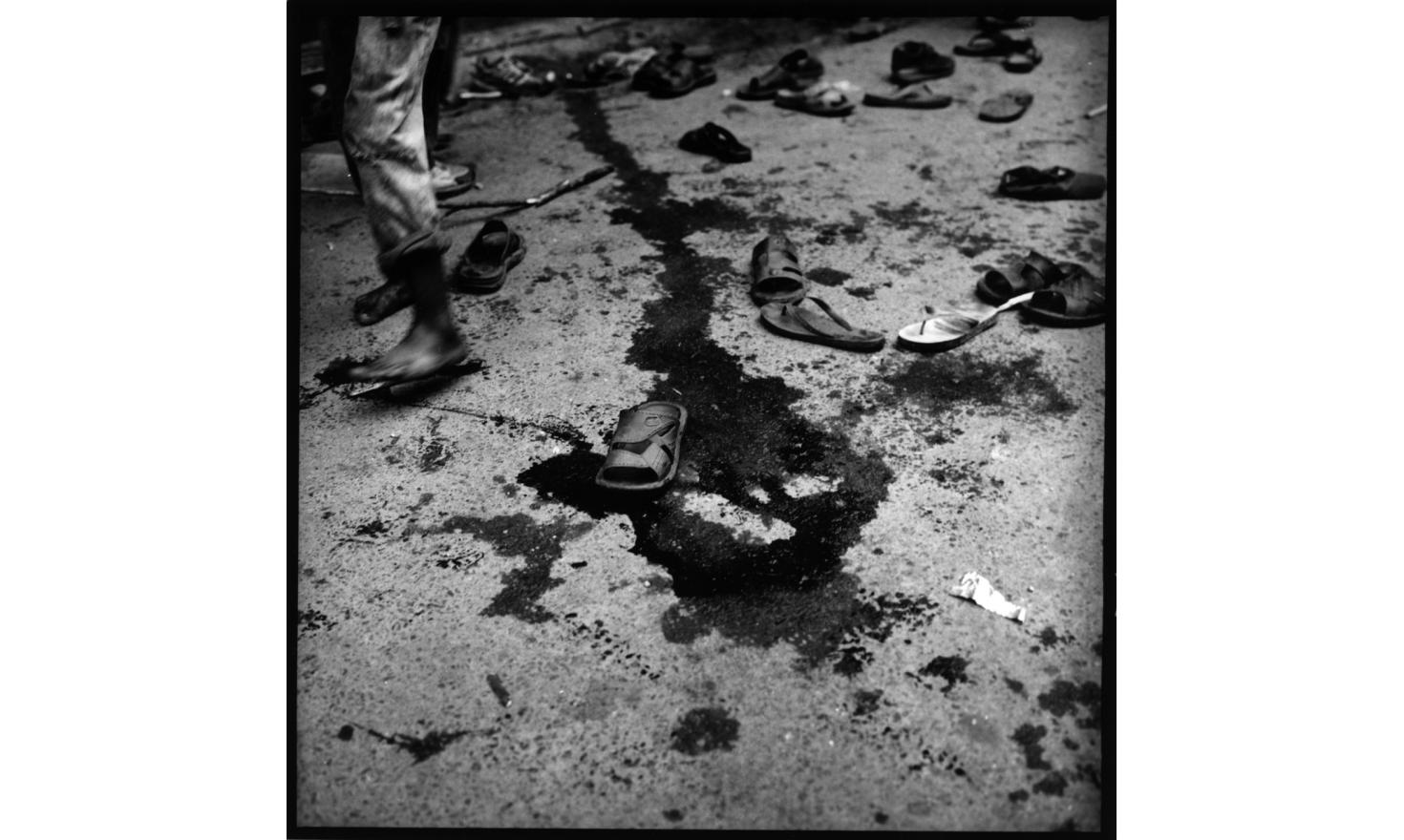 shoes of protestors who ran away or got injured by riot police, Asan chowk, Center of Kathmandu. The blood track belongs to a very young boy who got his head wide open by police bamboo stick. 22d of April 2006 Katmandu Nepal
