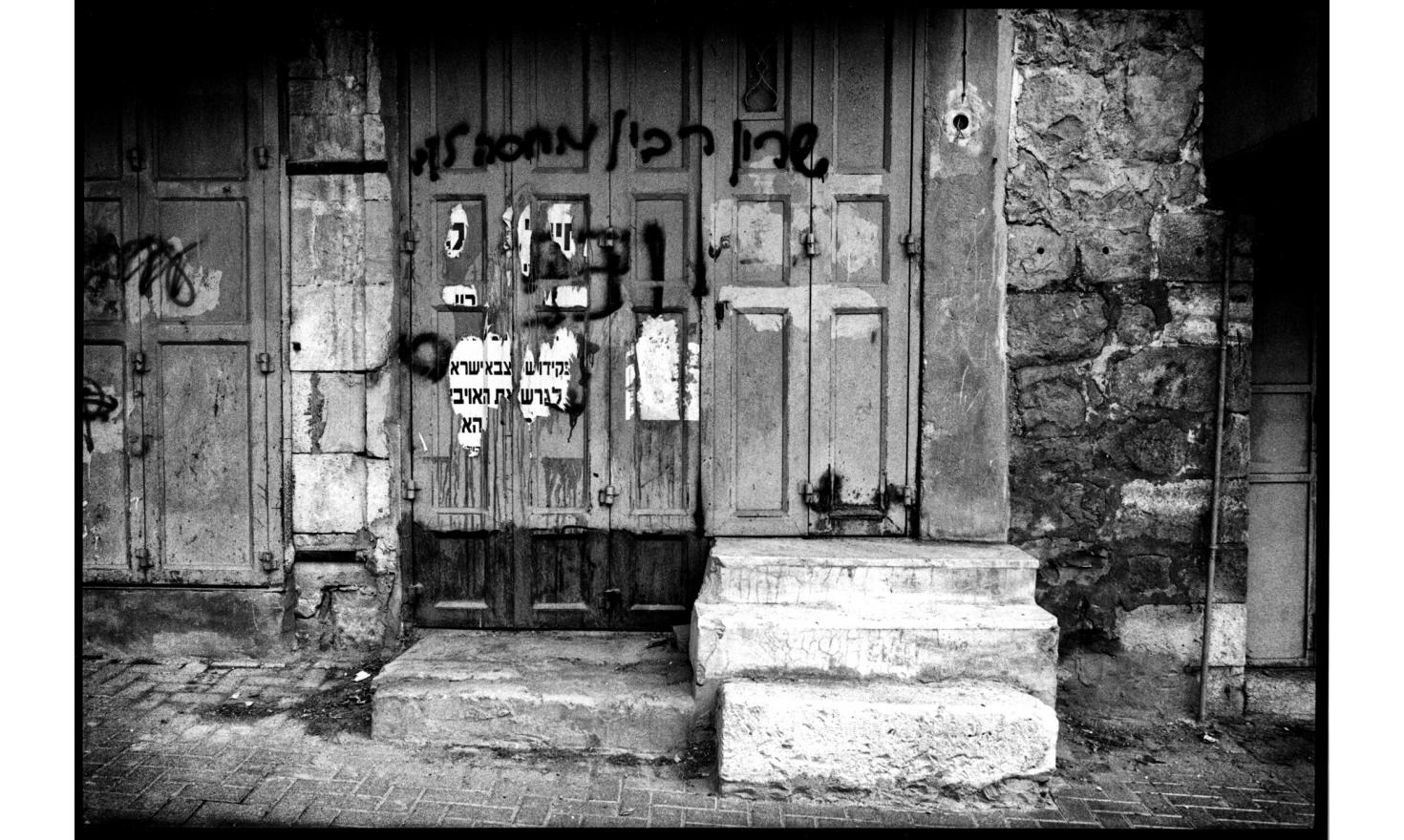 """In the bazaar, occupied by settlers, there are hostile inscriptions to the Pr. Minister, painted on doors of closed Arab shops, it is written: """"Sharon, Rabin is waiting for you"""": 6 weeks later, A. Sharon was struck by a cerebral attack. Hebron, Nov. 2005"""