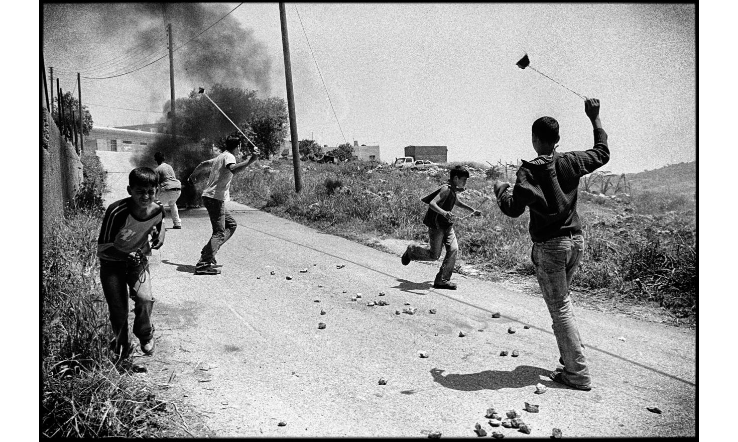 Clashes against the construction of the security fence, between palestinian youths and the israeli army. Biddu, occupied West bank. April 2004.