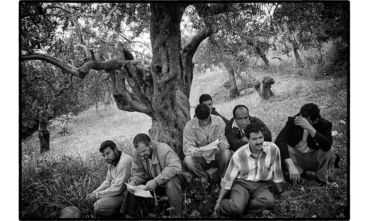 Men resting after paying their respect to the family of a young palestinian killed during a demonstration against the building of the security fence in their village. Biddu, West Bank. April 2004.