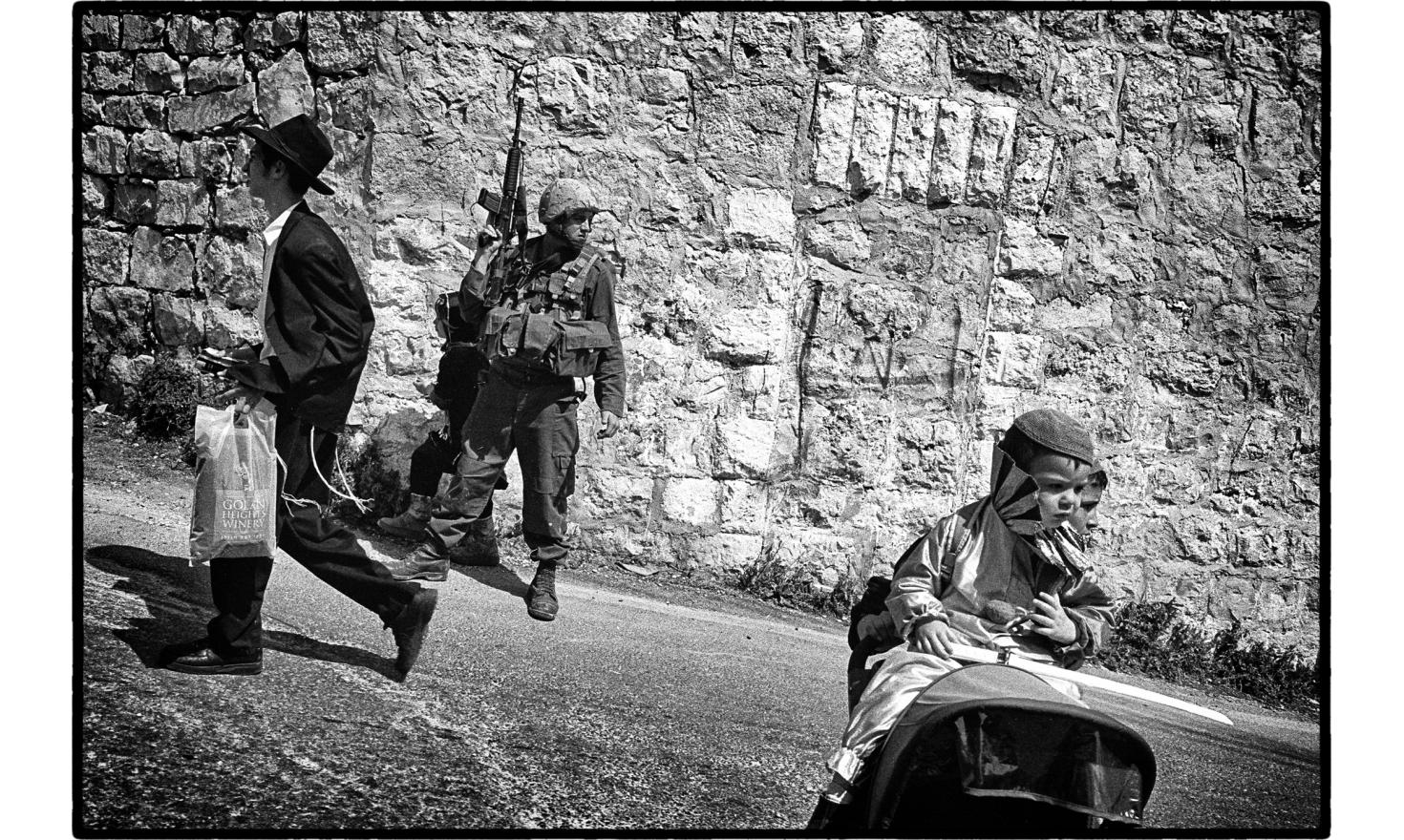 The celebration of Purim in Hebron is under the protection of the israeli army. Hebron, West bank. March 2005.