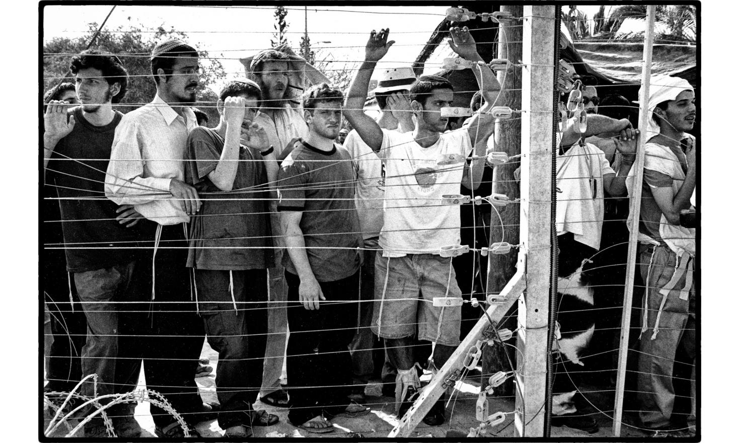 Young israeli settlers at the gate of a Gush Katif settlement. They refuse to leave and are waiting for the israeli army to dislodge them. Gush Katif, Gaza. August 2005.