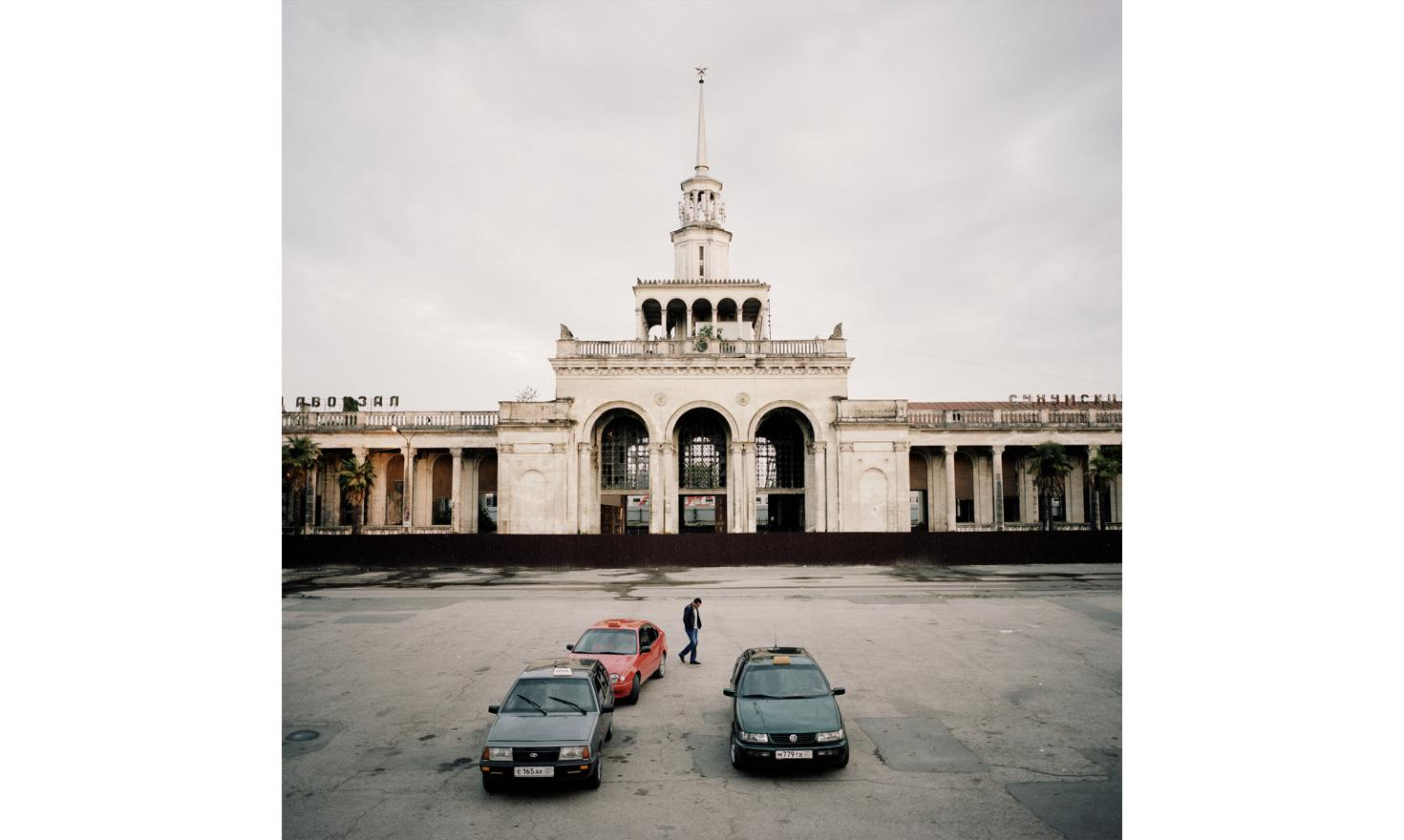 A man walk in front of the Sukhum(i) train station which is under renovation.