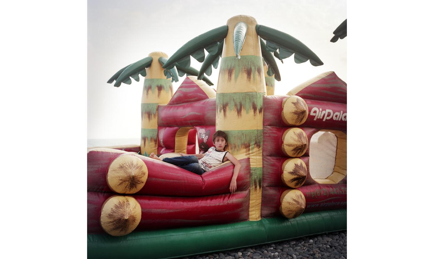 A young boy on a bouncy castle on Sukhum(i) Beach.