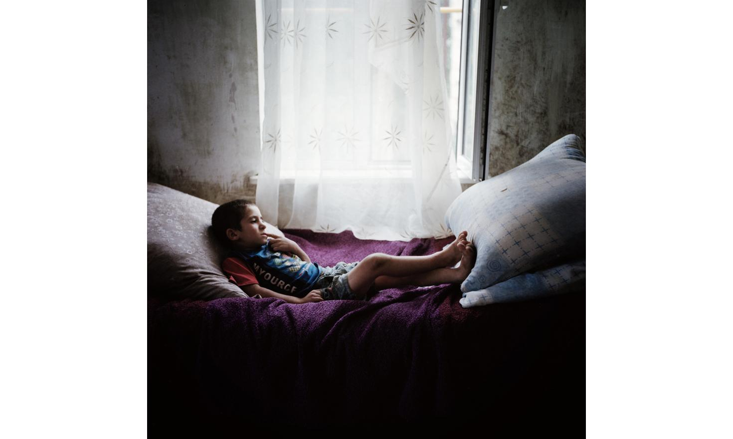 In Chouchi, a little boy from a large family in his bed, thoughtfully.