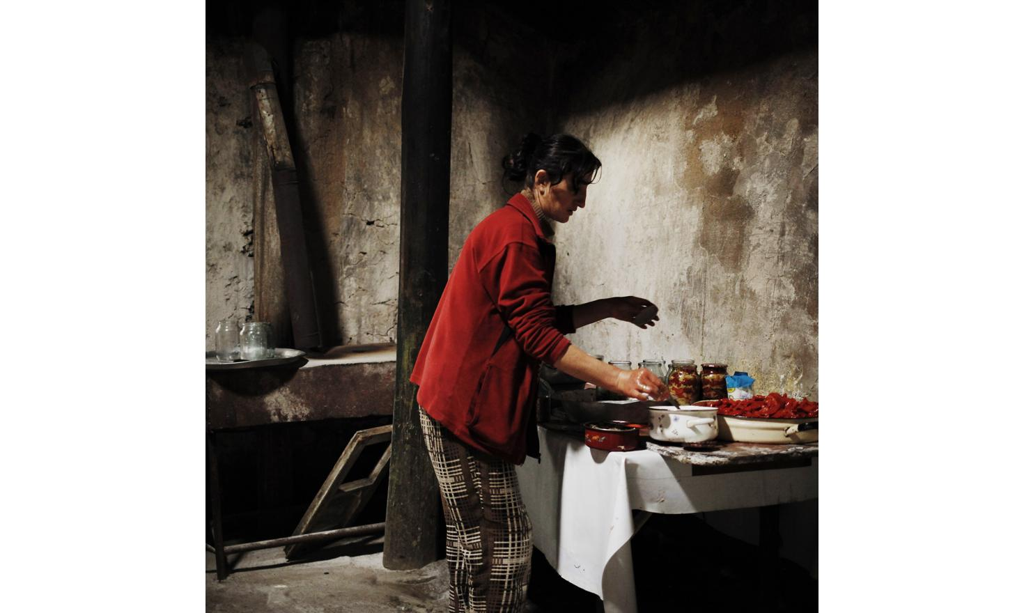 Anoush is preparing canned peppers in the outbuilding of the house.