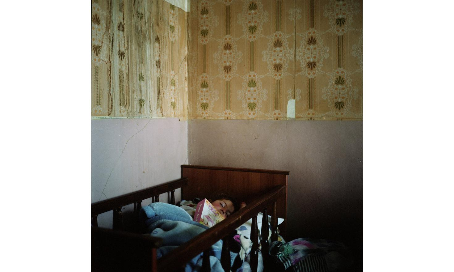 Lilith, Anoush's daugther, fell asleep with the photo album of her father. He went to Russia to work for years to earn money to build them a house in the village.