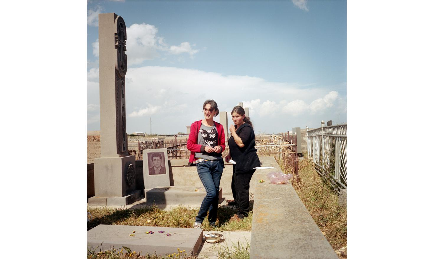 Today is the feast of the dead, the villagers go to the cemetery. They burn incense on the graves and will leave candy as offering. Ana (left) and Elvira (right) (cousins by marriage) go there together. Their husbands are in Russia.