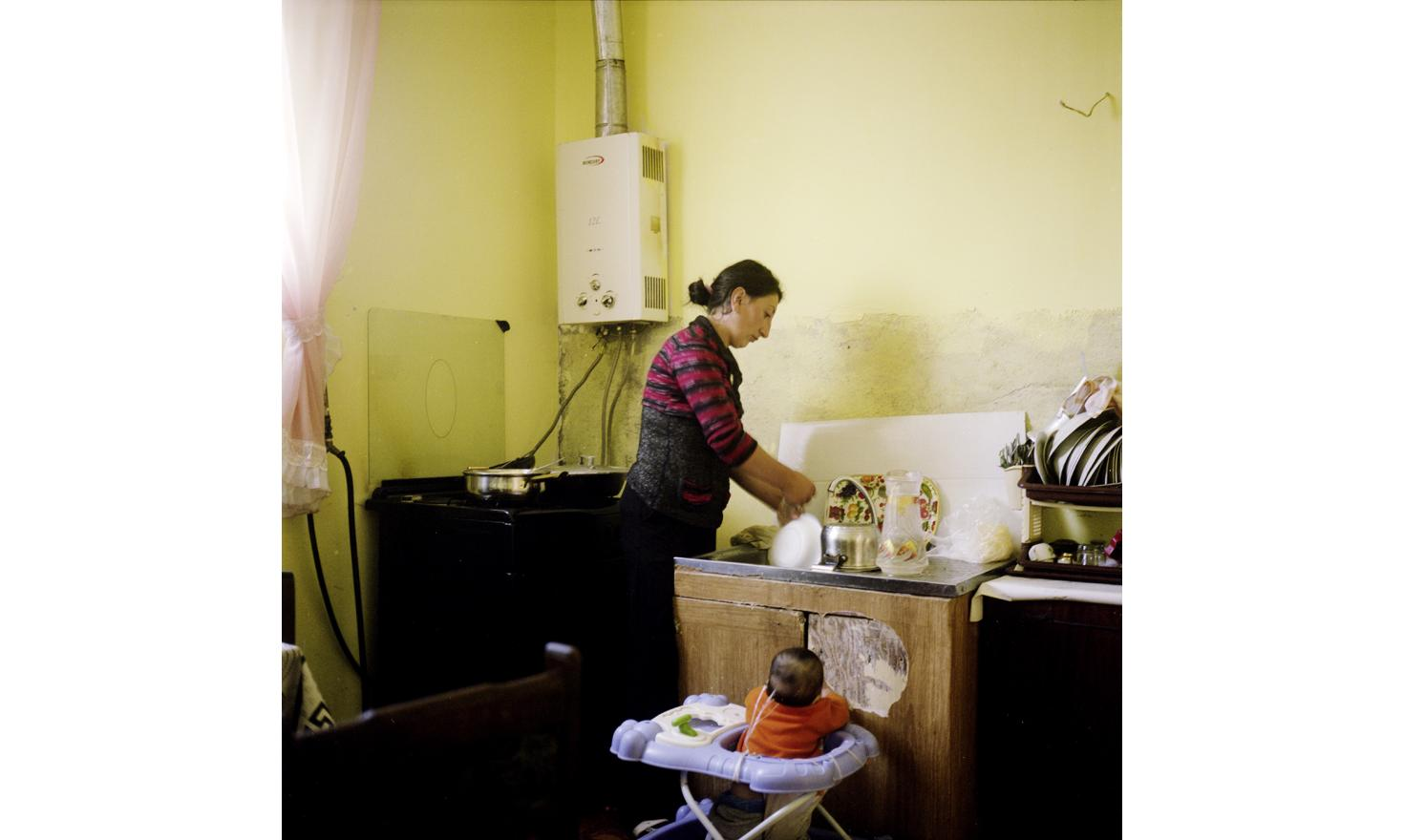 At Anoush's and Ruzanna's house. Ruzanna is doing the dishes while she must keep a look on her young daughter Naïre
