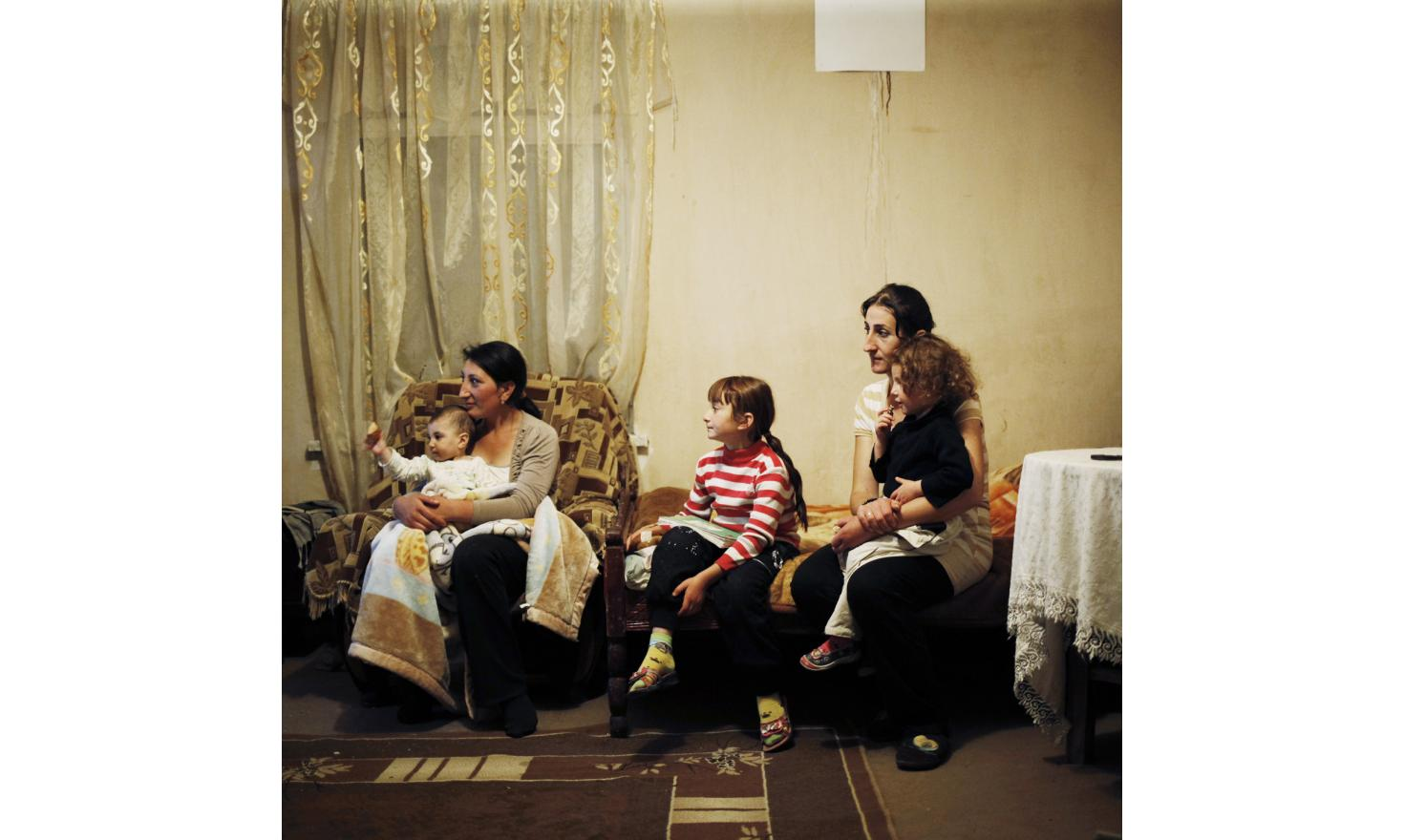 Anoush and Ruzanna are watching TV with three of their children.