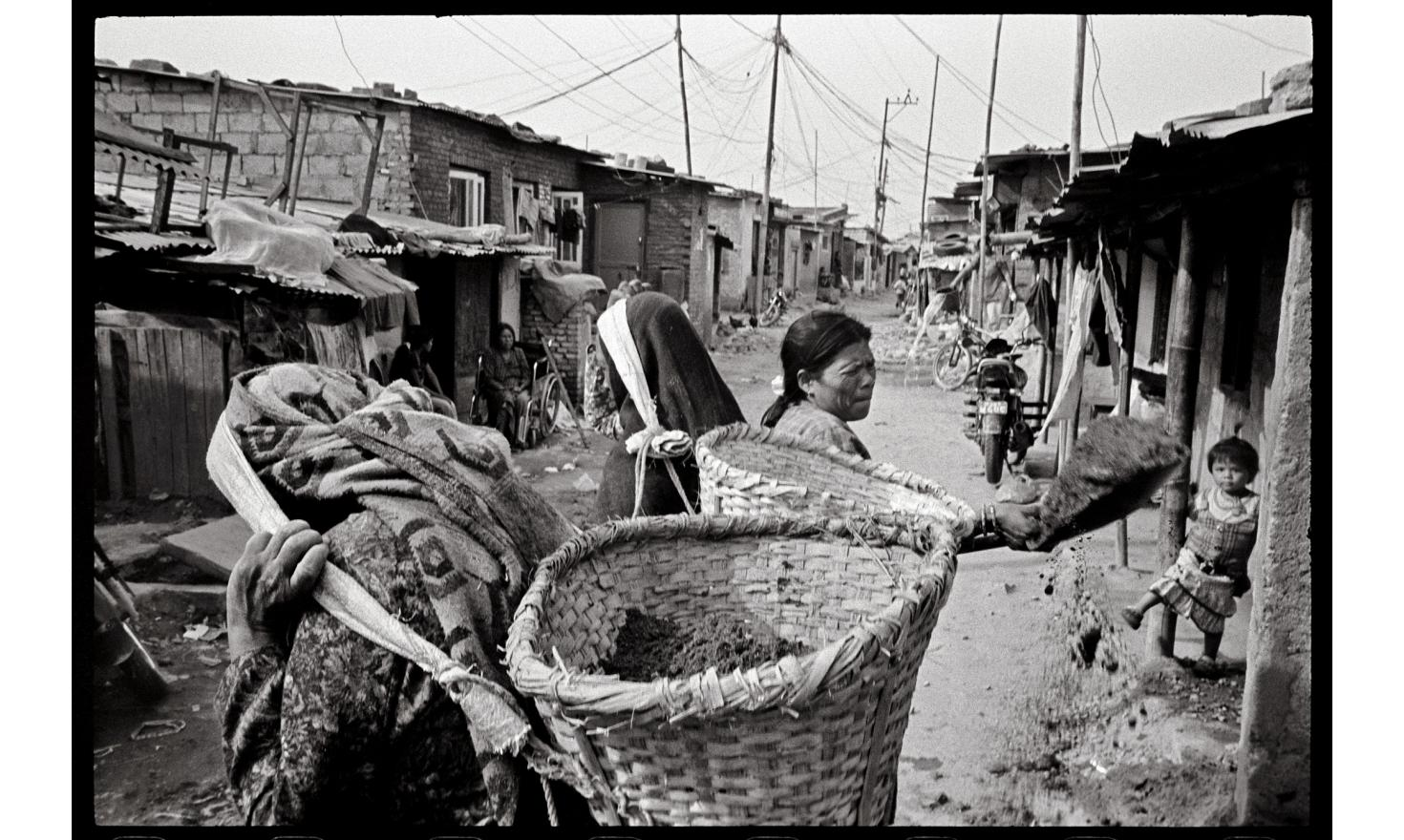 Manohara slum, Kathmandu Nepal. In Manohara, the biggest of Kathmandu's 63 shantytowns, migrant women struggle to make a living. Some grow vegetables to sell in the city markets ; others are exploited in the sweatshops of the slum.